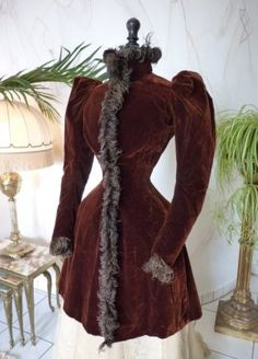 Long brown velvet jacket, ca. 1891. Gigot sleeves – typical for the fashion from this time. Trimmed in brown feathers to stand collar, cuff, front edge and flanking back vent. Brown silk lining.