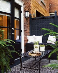 Black and white patio space with tiled floor and lots of plants