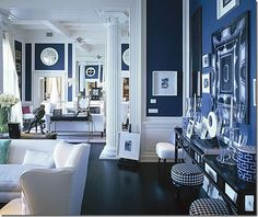 A luxurious living room with a blue theme, and a lot of interesting elements used for the overall design. Huge floor to ceiling windows and some tall white columns gives the feeling of an airy space, inspired from the rooms of the Greek kings.