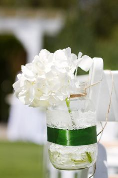 Mason jar wrapped in white lace and green ribbon