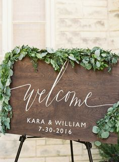 Rustic wooden eucalyptus covered wedding sign: http://www.stylemepretty.com/texas-weddings/austin/2016/10/22/classic-country-club-wedding-4/ Photography: Mint - http://mymintphotography.com/