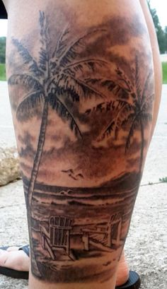 Another grayscale beach tattoo on the leg. The palm trees are drawn to stand strong and tall on the beach while there are two beach chairs on the shore facing the waves; a truly tranquil scene.