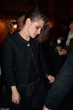 Classic ensemble: Kristen wore a classic boucle cardigan over a black top and trousers for...