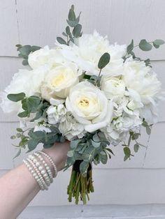 Elegant white bridesmaid's bouquet composed of peonies, stock, garden roses, ranunculus, and eucalyptus // wedding, natural, bride