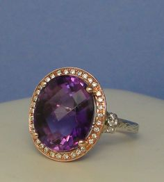 Oval Amethyst set in 14K rose gold diamond halo on white gold engraved band...