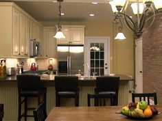 love the cream cabinets with light green wall and dark touches