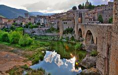 BESALÚ. Besalú es una población medieval situada a 150 metros de altitud en la provincia de Girona. Caminar por sus calles te hará detenerte en el tiempo. Estas, junto con sus piedras y su arquitectura se entremezclan para crear uno de los pueblos medievales mejores conservados y más bonitos de España.