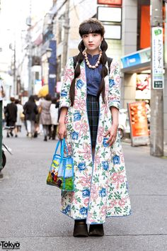 Akina's look features a long resale floral coat over a resale mandarin collar top,a plaid pleated skirt from Eastboy, and Buffalo platform shoes. Accessories – some of which came from a flea market – include her necklace, a headband, a Teletubbies tote bag, and a resale Eastpak backpack. Harajuku, spring, 2015.