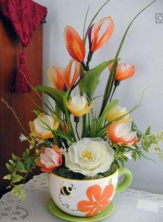 Hermoso arreglo con flores de nylon en una taza jardinera