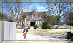 """The Blue Bell Tavern: This small blue home the """"Blue Bell"""" tavern or ordinary, located behind the Capitol. It is a great example of colonial architecture with symmetry, small multi-paned windows and large exterior fireplace."""