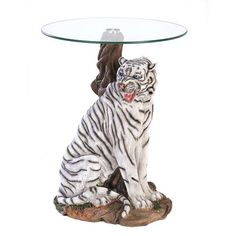 A rare white tiger is captured in all his beauty and might, forming a stunning sculptural base for a furnishing of singular distinction. Each detail of this stately statue is lovingly rendered for absolute lifelikeness. POLYRESIN TEMPERED GLASS : x x each
