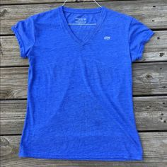 Blue workout tee In good used condition with no rips or stains but some minor pilling. Dry-wick performance tee. The true color is the last photo. This top is more of a purplish blue than true blue. Thanks for looking. Marika Tops Tees - Short Sleeve