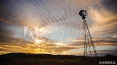 Stock Video of Dramatic linear timelapse sunrise with scattered clouds changing color with a silhouetted windmill in the foreground in a scenic landscape setting with a mountain range in the background available on request. at Adobe Stock Mountain Range, Windmill, Stock Video, Geology, Stock Footage, Wind Turbine, South Africa, Sunrise, Adobe