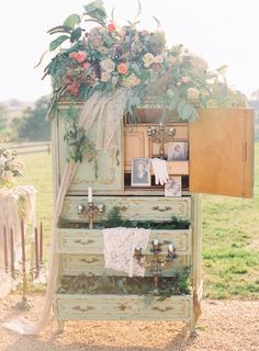 Tall pastel green and gold vintage chest of drawers used as wedding ceremony decor with vintage candlesticks and stunning florals by Holly Heider Chapple Flowers, Ltd. Image by Jodi Miller Photography at Shadow Creek in Purcellville, VA.