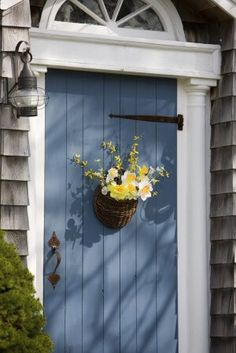 An old-fashioned wooden house. The front door is old-fashioned as well, and is painted blue. It has a rusty door handle and door hinges. A flower basket is hanging right in front of the door. A door lamp is installed right beside the door. It also has a wooden transom above it and a pair of columns painted in white.