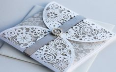 Grey and white wedding invitations, elegantly enclosed with ribbon and pearls.