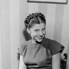 A cheerfully smiling 1940s teenager shows off her lovely braided updo