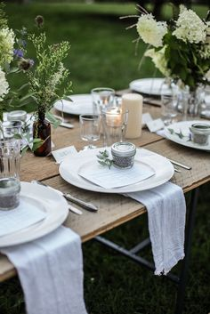 Outdoor dining in a park | white cloth napkins + floral table scape