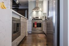 Home Depot: bright, lacquered white uppers, and contrasting lower cabinets in a striated grey laminate. A quartz countertop gives the look of marble, with a lot less maintenance,