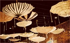 vintage umbrellas hover over tables with strings of dripping crystals that  resemble raindrops.