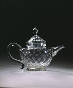 """1760-1780 British Teapot(?) at the Victoria and Albert Museum, London - From the curators' comments: """"Thoroughly impractical as a container for boiling water, this glass pot may have been intended for serving some attractively-coloured sauce. Table glass items with overall facet-cutting were usually intended for the dessert table, where the candlelight would enhance their appearance."""""""