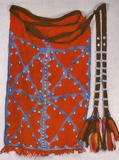 Traditional bridal 'ön gerge' (apron) from the village of Merkez Kapıkaya (Kozak Yaylası, near Bergama), ca. 1975.  Ethnic group: Alevi Türkmen.  Woollen fabric, adorned with blue cotton patchwork & white buttons; the down edge framed with 77 small woollen tassels.  A card-woven woollen belt (woven by Yörüks) is attached to it, and adorned with tassels, glass beads, shells and buttons.  (Source: 'Türkmen Giyimi', Sabiha Tansuğ).