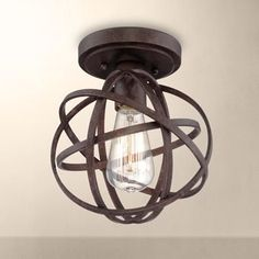 Perfect for industrial style decor, this ceiling light features a handsome bronze finish, ato an open cage design, and a decorative Edison-style bulb.