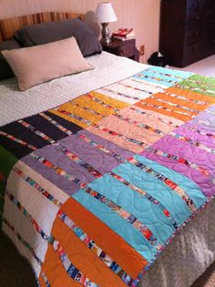 Bright Birch quilted bed runner. Love the use of scraps to make bands of color and solids.