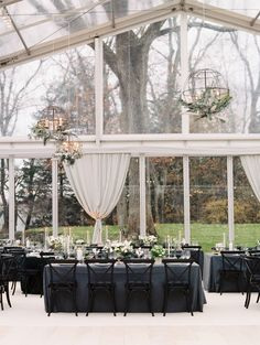 glass reception room with black wedding chairs and grey linens | Photography: Leila Brewster