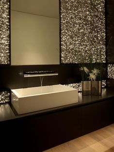 This bathroom has some Vegas glitz with a dramatic wall-mounted faucet and metallic walls.