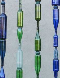 Glass bottles skewered on metal poles create a whimsical fence element! or one wooden dowel rods seems like it would make more sense...maybe a wooden bead in between then so glass isnt rubbing on glass. ...