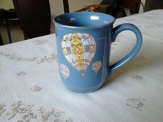 """Mug in a multicolored hot air balloon display on a blue background, gold accenting   This mug is 4"""" (10.2 cm) high x 3 1/8"""" (7.9 cm) at the brim   There is a slight fleabite (see last photo) on the brim but otherwise this mug is in very good condition   Made in Japan by Curtis-Swann"""
