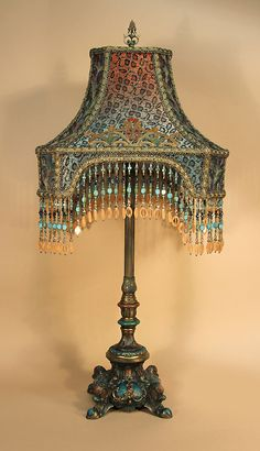 Handsome and ornate, painted metal table lamp holds a 'LONDON BRIDGE' shaped shade, ombre dyed coral into turquoise, covered with two different black silk net, shot with gold metallic, laces; then, overlaid with old velvet appliqués. Hand beaded fringe.