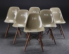 Charles Eames. Six shell chairs, model DSW, fibreglass stained army-green. Early version of the fibreglass shell produced by Zenith Plastics 1950-1953. Chairs were used outdoors and have five drain holes for rainwater in the seats. Numbered on backs. Labels from Zenith and Herman Miller embossed in shells.   Dark wooden Dowel legs of later date. Shells are restored, small scratches and minor marks. Bases with marks, scratches and minor chips. Some bases tilt and have different screws.