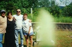 MEMORIAL DAY APPARITION! Family visiting the grave of their parents on Memorial Day gathered for a family pic. What could be ghost next to them?