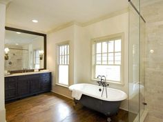 """Rustic Feminine Bath Retreat: A novel component of this luxury home is the existence of two master bathrooms. Viewed here is the """"hers"""" portion of the space with a clawfoot tub and separate shower. From HGTVRemodels.com"""