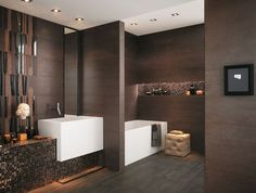 modern bathroom design with dark color on the wall and floor, white basin with modern faucet, white bathtub and cream upholstered stool