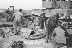 """Engine Repair in a tiger with the tactical number 141 of the schwere-Panzer-Abteilung 501 in North Africa. Next to the tank, the two """"Feifel"""" purifiers, the flexible tubes and the lining of the mufflers are awaiting to be prepped for storage. A captured Dodge WC52 (4x4) LKW0.75 t (4x4) serving the armored-maintenance as a tool truck."""