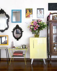 O mix de espelhos e pôsteres é uma ideia superbacana para decorar a parede. A minigeladeira retrô e a cristaleira antiga completam o look descolado do ambiente, que fica no apartamento da confeiteira @carolecrema.: Estúdio Pulpo#revistacasaclaudia #decor #decoração #homedecor #decoracaodeinteriores #parede #interiordesign #carolecrema