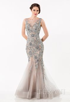 Sleeveless tulle gown with lace underlay, all over floral themed embellishment, simulated one shoulder neckline, and flared hemline.