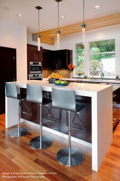 Moving+into+the+kitchen+space,+we+have+a+bold,+two+tier+island+with+minimalist+white+dining+area+and+lower+cooktop+space.+Modern+look+stainless+steel+bar+stools+providing+seating+beneath+a+trio+of+slim+pendant+lights.