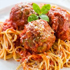 Grandma's Italian meatball recipe is the ultimate comfort food to share with the family! Tender and juicy meatballs simmered in a simple yet rich tomato sauce and placed over spaghetti noodles or the pasta of your liking. #italianfood #meatballs