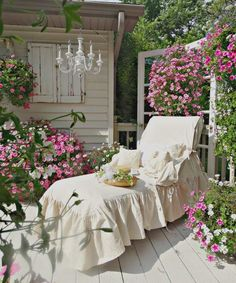 terrasse banche de style Shabby chic avec un brise-vue en vieille porte, banc avec couverture blanche et beaucoup de pétunias en rose et blanc