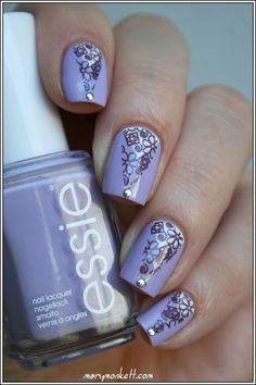 Essie 'Lilacism' ~ 2 coats (a true purple with touch of gray). At nail base, a small triangle created with masking tape and white polish. Again a larger triangle created with masking tape and stamped over with a Cheeky plate flower pattern using A England 'Sleeping Palace'. A small stud to finish. ~ by Mary Monkett