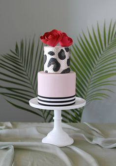 Two tier peppermint cake by Charm City Cakes. Bottom tier is soft pink with black and white stripes on bottom. Top tier is pearl white with black patterns, topped with two red roses.