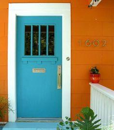 Opposites attract - orange house, blue Craftsman style front door.