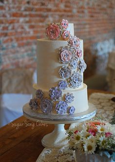 """Steampunk """"Light"""" Wedding Cake - The invitation's gear and industrial sketches inspired this industrial romantic design.  Vintage ruffle flowers are set upon silver gears and cascade down the cake from blush to dove grey to lavender. Cake is 10"""", 8"""",8"""", 5""""short and finished in ivory buttercream with pearl spray finish."""