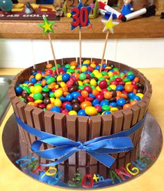 Kit-Kat framed chocolate cake, topped with mixed M&Ms tied with ribbon