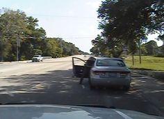 Der Beamte zerrt die Frau gewaltsam aus dem Wagen.
