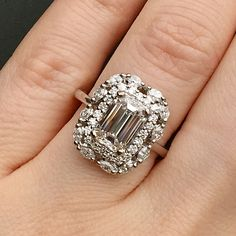 A unique twist on a halo engagement ring with 1.52ct center emerald cut diamond.